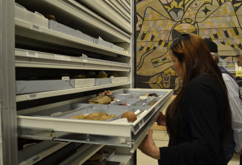 Woman looks into a drawer of indigenous artifacts in a storage area with many drawers and a Native American tapestry with a black, beige and grey design on the wall behind