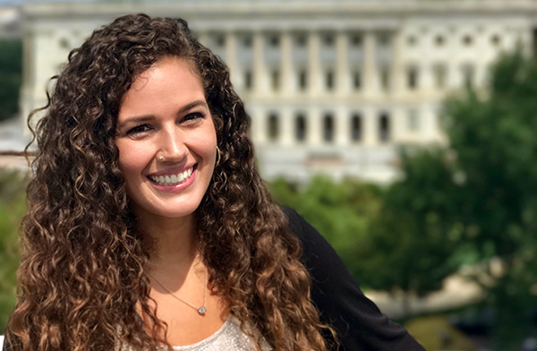 Smiling woman with long brown curly hair with U.S. Capitol building