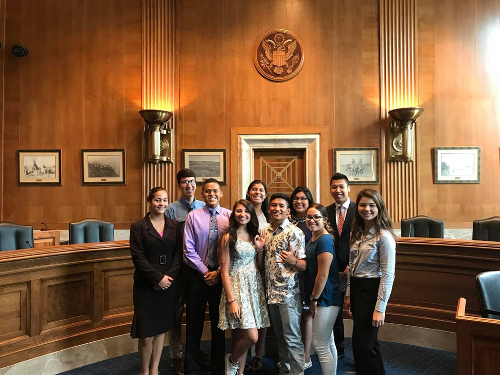 A group shot of 10 high school students partcipating in the Inspire Program posed in the US Senate building in front of wood paneled background