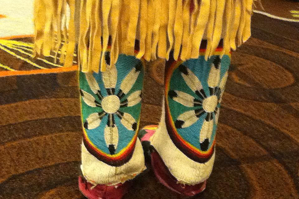 Two legs and feet in brightly colored native footwear with a turquoise circle and feather pattern and a leather fringe hanging down from a skirt