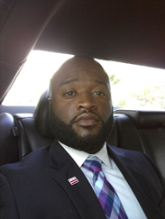Sean Floyd African American man headshot in a suit in a car with a multicolor tie