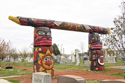 2 tall red and yellow wooden Totem poles with a horizontal connector laid across them in Congressional Cemetery