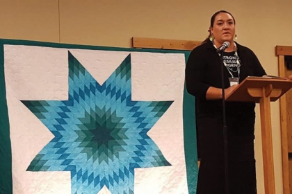 Woman in black outfit standing at a podium next to quilt blanket with a blue star pattern on a white background.